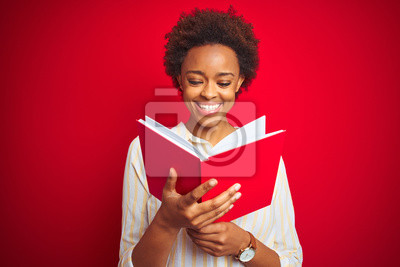 Naklejka African american woman reading a book over red isolated background with a happy face standing and smiling with a confident smile showing teeth