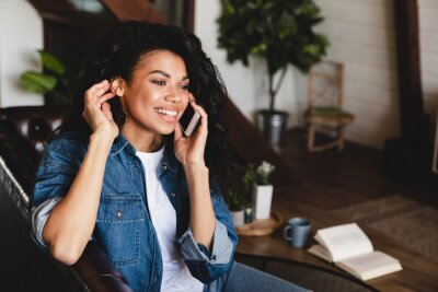 Naklejka African-american young woman talking on phone in her cosy house. Businesswoman working from home office and using cell phone. Beautiful afro american woman sitting at the desk in a home office.
