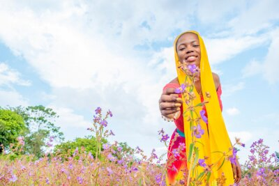 Naklejka african girl picking flowers in a field