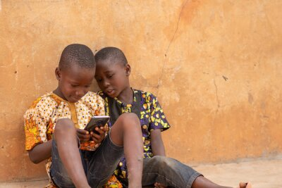 Naklejka african kids using a smartphone. two african children viewing content on a mobile phone together