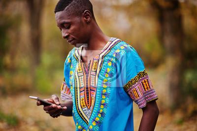 Naklejka African man in africa traditional shirt on autumn park.