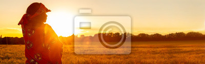 Naklejka African woman in traditional clothes in field of crops at sunset or sunrise panorama