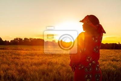Naklejka African woman in traditional clothes standing in a field of crops at sunset or sunrise
