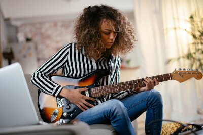 Naklejka African woman with guitar. Beautiful woman playing guitar.