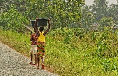 Naklejka Afrykańscy nastolatkowie niosą bagaż na głowach. Młode afrykańskie dziewczyny idą wzdłuż drogi. Wieś. Styl życia w rozwijających się krajach Afryki. Ghana, Akra - 31 stycznia 2017 r