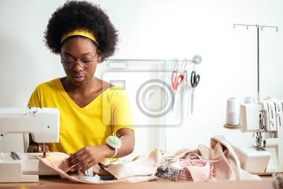 Naklejka afrykańska szwaczka szyje ubrania. Miejsce pracy krawca - maszyna do szycia, rolki nici, tkaniny, nożyczki.