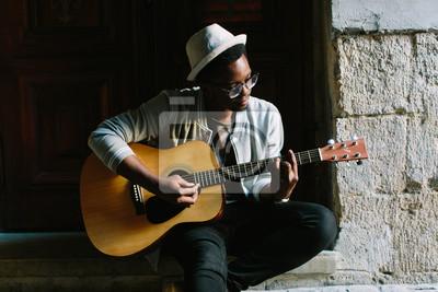 Naklejka Afrykański muzyk bawić się gitarę w mieście