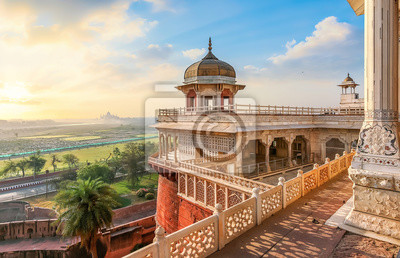 Naklejka Agra Fort - Medieval Indian fort made of red sandstone and marble with view of dome at sunrise. View of Taj Mahal at a distance as seen from Agra Fort.