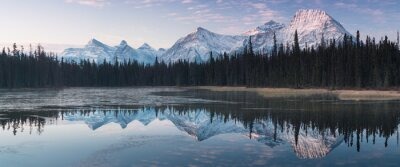 Naklejka Almost nearly perfect reflection of the Rocky mountains in the Bow River. Near Canmore, Alberta Canada. Winter season is coming. Bear country. Beautiful landscape background concept.