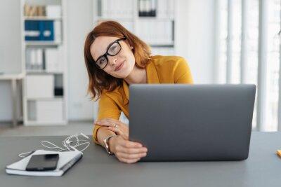 Naklejka Amused businesswoman peering around her laptop