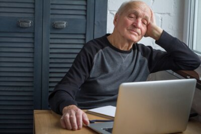 Naklejka An elderly man is tired of looking at the screen of an open laptop, counting taxes, selective focus, free space for text.