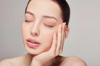 Naklejka An elegant sophisticated beautiful girl with full lips, brown hair and clean delicate skin on the gray background. Lady put her head on her hand. Close eyes. Spa, face skin care. Wellness.
