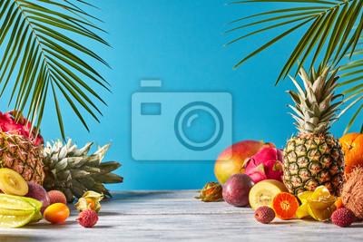Naklejka Ananas, mango, owoc smoka, marakuja, kokos, carambola, kumkwat - rama egzotycznych owoców z liśćmi tropiku na niebieskim tle.