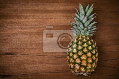 Naklejka Ananas na drewnianym stole górnym widoku