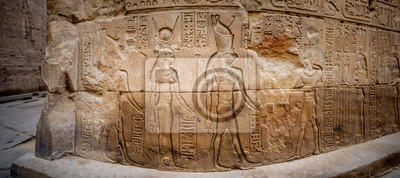 Naklejka Ancient Egyptian hieroglyphs and relief drawings on one of the walls of the Edfu complex. Temple of Edfu, Nubia, Egypt.