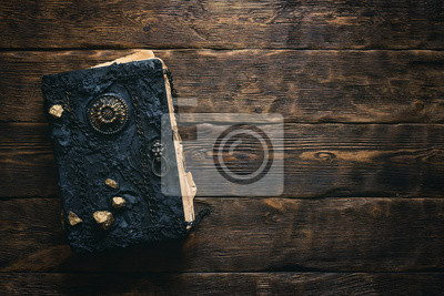 Naklejka Ancient magic book on a wooden table background with copy space. Spellbook.