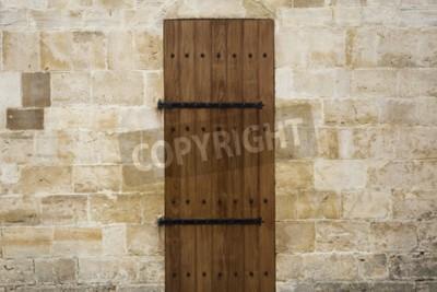 Naklejka Ancient wooden door in old stone wall