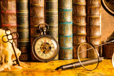 Naklejka Antique clock on the background of vintage books. Mechanical clockwork on a chain. Fountain pen and glasses.