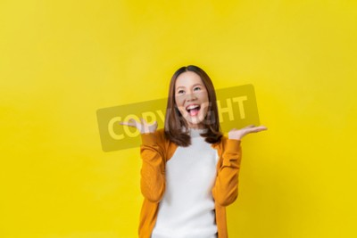 Naklejka Asian girl is surprised. She is excited.Yellow background studio