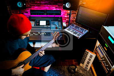 Naklejka asian male musician recording acoustic guitar track in home studio