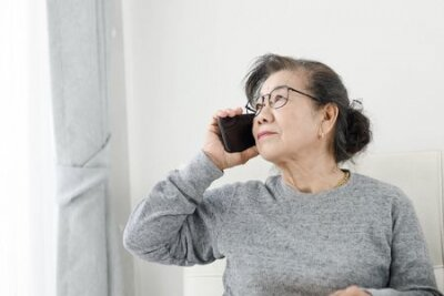 Naklejka Asian senior woman make a phone call white sitting on sofa at home, lifestyle concept.