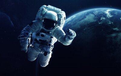 Naklejka Astronauta przed planetą Ziemi. Elementy tego obrazu dostarczone przez NASA