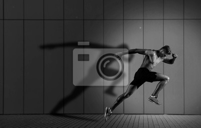 Naklejka Athletic man sprinter running on dark wall background