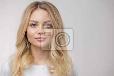 Naklejka atrakcyjna kobieta o długich, jasnych włosach patrzących w obiektyw. pojedyncze białe tło