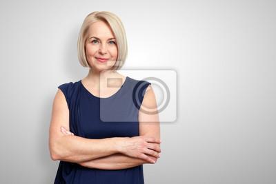 Naklejka Atrakcyjna kobieta w średnim wieku z założonymi rękami