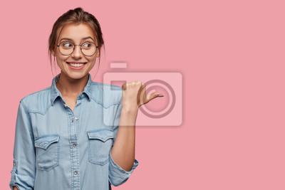 Naklejka Atrakcyjna kobieta z radością wyrażania radości używać tej przestrzeni kopii mądrze, ubrana w modną kurtkę dżinsową, punkty z kciukiem na bok, modele na różowym tle. Idź w tym kierunku.