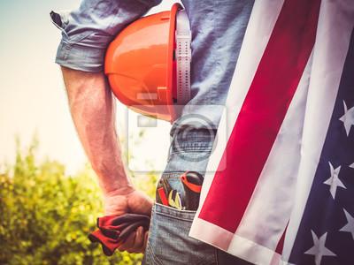 Naklejka Atrakcyjny mężczyzna w odzież roboczą, trzymając narzędzia i flagę USA w jego ręce i patrząc na odległość na tle drzew, błękitne niebo i zachód słońca. Widok z tyłu. Koncepcja dnia pracy