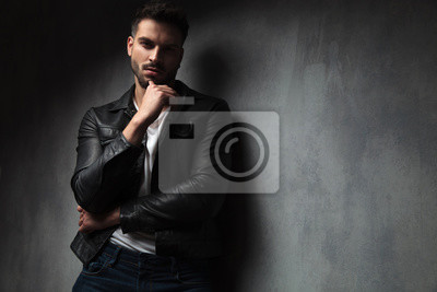 Naklejka attractive man in leather jacket with finger on his chin