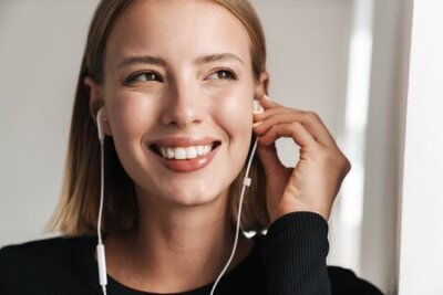 Naklejka Attractive smiling young blonde short haired woman leaning on a wall while standing indoors, listening to music with earphones