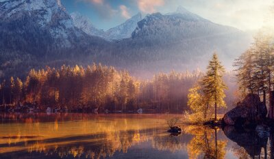 Naklejka Awesome Nature Scenery. Beautiful landscape with high mountains with illuminated peaks, stones in mountain lake, reflection, blue sky and yellow sunlight in sunrise. Amazing nature Background.