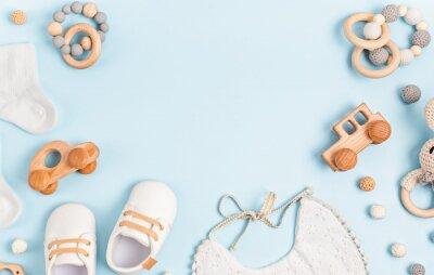 Naklejka Baby shoes, bib and teether on pastel background. Organic newborn accessories