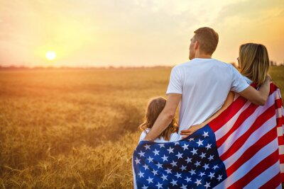Naklejka Back view of a unrecognizable Happy family in wheat field with USA, american flag on back.