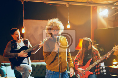 Naklejka Band practicing for the gig.  Male singer with curly hair holding microphone and singing. In background band playing instruments. Home studio interior.