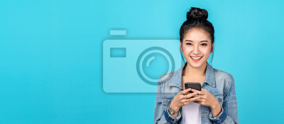 Naklejka Banner of Portrait happy asian woman feeling happiness and looking camera holding smartphone on blue background. Cute asia girl smiling wearing casual jeans shirt and connect internet shopping online