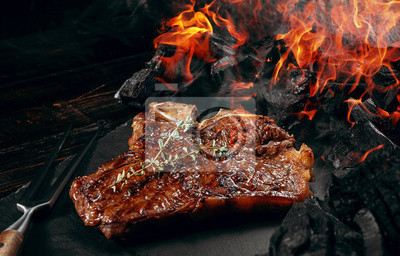 Naklejka barbeque steak on a black slate board with meat fork and grill coals next to it