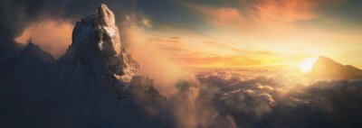 Naklejka Beautiful aerial landscape of mountain peak at sunset above the clouds - panoramic