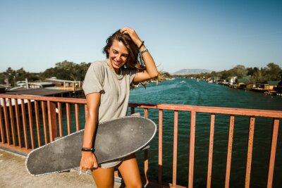 Naklejka Beautiful and fashion young woman posing with a skateboard.