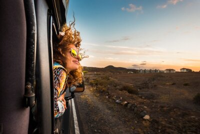 Naklejka beautiful caucasian young woman travel outside the car with wind in the curly hair, motion and movement on the road discovering new places during a nice sunset, enjoy and joyful freedom concept