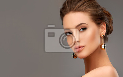 Naklejka Beautiful girl . Fashionable and stylish woman in trendy jewelry big earrings .  Fashion look  , beauty and style. Natural makeup & easy styling