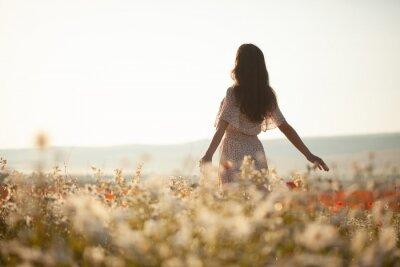 Naklejka Beautiful girl in summer dress walks in a flower field