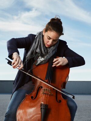 Naklejka beautiful girl plays the cello with passion in a concrete environment