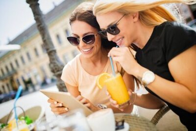 Naklejka Beautiful girls having fun smiling together in a cafe outdoor