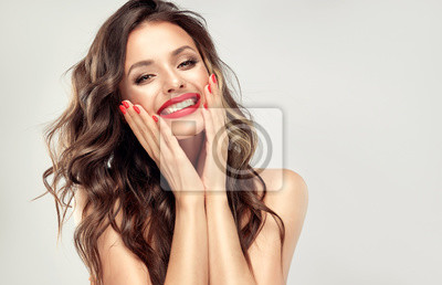 Naklejka Beautiful laughing brunette model  girl  with long curly  hair . Smiling  woman hairstyle wavy curls . Red  lips and  nails manicure .    Fashion , beauty and make up portrait