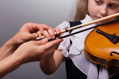 Naklejka Beautiful little girl playing the violin on gray background