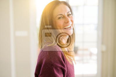 Naklejka Beautiful middle age woman smiling at home