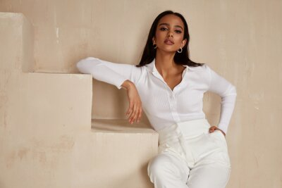 Naklejka Beautiful sexy brunette woman tanned skin face cosmetic makeup wear white suit pants for date walk office fashion clothes style collection interior room  sand color safari summer casual.